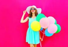 有空气五颜六色的气球的时尚愉快的俏丽的微笑的妇女获得穿在桃红色背景的乐趣一个夏天草帽 库存照片