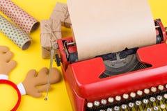 有空白的工艺纸、礼物盒和包装纸的红色打字机在黄色背景 免版税库存图片