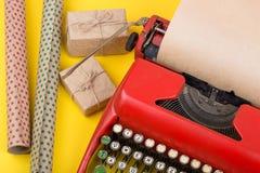 有空白的工艺纸、礼物盒和包装纸的红色打字机在黄色背景 库存照片