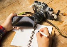 有空白的手机、日志和老照相机的女孩 免版税库存图片