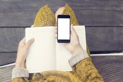 有空白的手机屏幕和空白的日志的女孩在木benc 库存图片