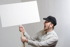 有空白的抗议标志的恼怒的抗议的工作者 免版税库存图片