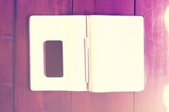 有空白的日志的空白的黑智能手机屏幕在木桌上, 免版税库存照片