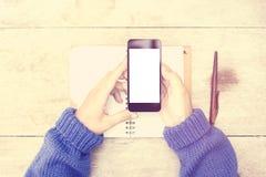 有空白的智能手机屏幕和日志的女孩在木桌上 图库摄影