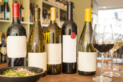 有空白的标签、葡萄酒杯和碗的酒瓶沙拉 库存照片