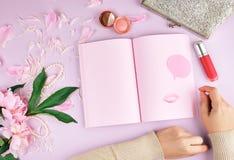 有空白的桃红色页的开放笔记本,牡丹花束,红色口红和一台女性银色传动器 免版税库存照片