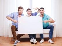 有空白的白板的愉快的男性朋友在家 免版税图库摄影