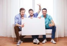 有空白的白板的愉快的男性朋友在家 图库摄影