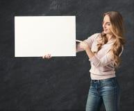 有空白的白皮书的年轻微笑的妇女 免版税库存图片
