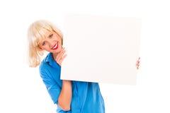 有空白的白色卡片的微笑的白肤金发的妇女。 免版税库存照片