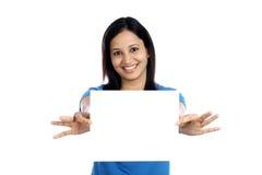 有空白的白色卡片的激动的少妇 库存图片