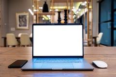 有空白的白色屏幕的便携式计算机在桌上 概念笔记本办公室笔手表 免版税库存照片