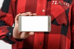 有空白的白色屏幕的智能手机水平地在女性手上 以红色格子衬衫女孩为背景 免版税图库摄影