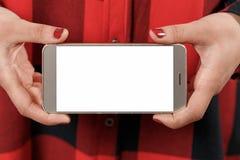 有空白的白色屏幕的智能手机水平地在女性手上 以红色格子衬衫女孩为背景 库存照片
