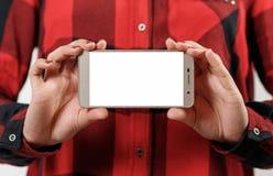 有空白的白色屏幕的智能手机水平地在女性手上 以红色格子衬衫女孩为背景 库存图片