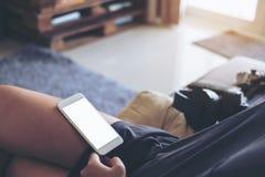 有空白的白色屏幕的白色手机在妇女` s大腿有灰色地毯背景在房子里 免版税库存照片