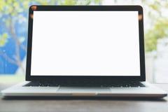 有空白的白色屏幕的膝上型计算机在木桌上有蓝天和自然背景通过镜子窗口 库存照片