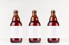 有空白的白色标签的三个棕色比利时steinie啤酒瓶500ml在白色木板,嘲笑  图库摄影