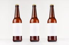有空白的白色标签的三个棕色longneck啤酒瓶500ml在白色木板,嘲笑  库存照片