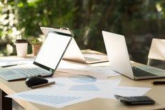 有空白的白色桌面屏幕的膝上型计算机在与没有的计算机的桌上 免版税库存图片