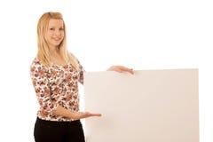 有空白的白色横幅的逗人喜爱的白肤金发的妇女被隔绝在白色ba 免版税库存照片