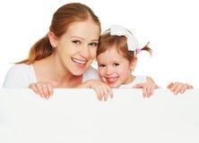有空白的白色海报的愉快的家庭母亲儿童女儿 免版税库存图片