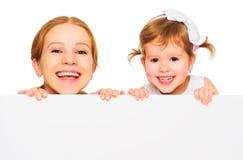 有空白的白色海报的愉快的家庭母亲儿童女儿 免版税库存照片