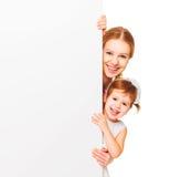 有空白的白色海报的愉快的家庭母亲儿童女儿 库存图片