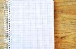 有空白的白页的被打开的螺旋装订的笔记本在表上 库存图片