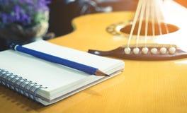 有空白的笔记本和铅笔的吉他弹奏者歌曲作者 库存图片