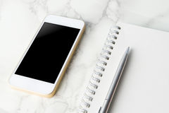 有空白的笔记本的空白的巧妙的电话屏幕在大理石 免版税库存图片