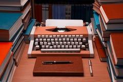 有空白的纸片的打字机与许多书的在backgrou 免版税库存图片