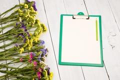 有空白的黄色纸的,铅笔,五颜六色的花绿色剪贴板 图库摄影