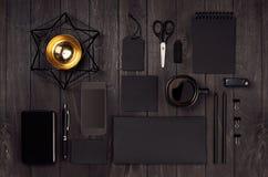 有空白的黑文具的,电话,咖啡,在黑暗的木委员会的金装饰现代时髦的工作地点 免版税库存照片