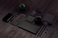有空白的黑文具的,电话,咖啡,黑暗的木委员会的绿色植物现代时髦的工作地点,倾斜 免版税图库摄影