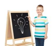 有空白的黑板的微笑的小男孩 免版税库存照片