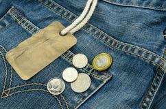 有空白的价牌的在背景的蓝色牛仔裤和硬币 库存图片