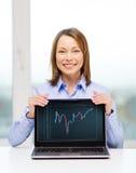 有空白的黑膝上型计算机屏幕的女实业家 免版税库存照片
