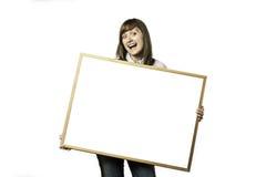 有空白的whiteboard的愉快的女孩 库存图片