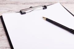 有空白纸的在一张木书桌上的剪贴板和笔 库存照片
