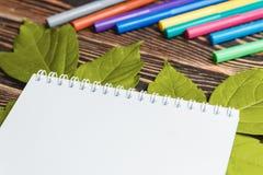 有空白纸的秋天叶子在木表上 免版税库存照片