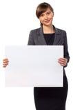有空白董事会的新微笑的妇女 库存图片