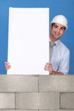 有空白面板的人在墙壁上 库存照片