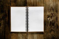 有空白页的一个开放笔记本在木桌上 免版税库存图片