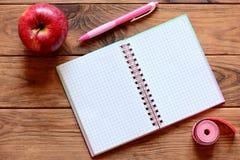 有空白页的纸笔记本,笔,苹果,测量的磁带在书桌上的厘米 锻炼和节食的日志与空的地方 免版税库存图片