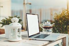 有空的屏幕大模型的膝上型计算机在室外的咖啡馆 免版税库存照片