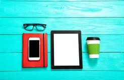 有空的屏幕的电子设备在蓝色木背景 咖啡、玻璃和笔记本 选择聚焦 免版税库存图片
