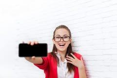 有空的拷贝空间穿戴红色夹克玻璃愉快的微笑的女实业家展示细胞巧妙的电话屏幕 免版税图库摄影