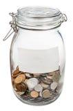 有空的标签和被保存的硬币的闭合的玻璃瓶子 免版税库存照片