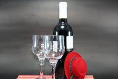 有空的标签的红葡萄酒瓶和在黑背景的两块玻璃 库存图片